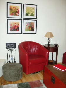 Red living room décor includes two leather chairs